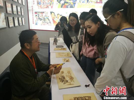 """刘凯的弟子时联峰向参观的学生介绍""""火笔"""" 刘浩 摄"""