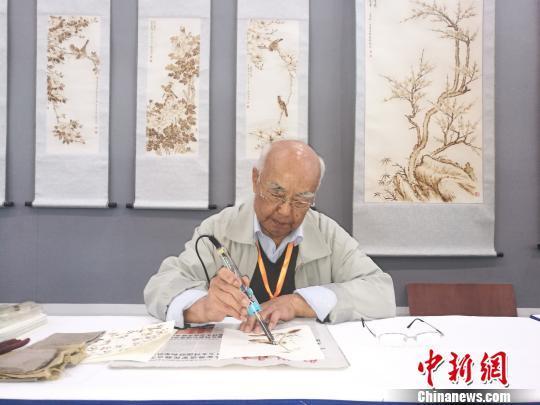 """刘凯手持""""火笔""""作画 刘浩 摄"""