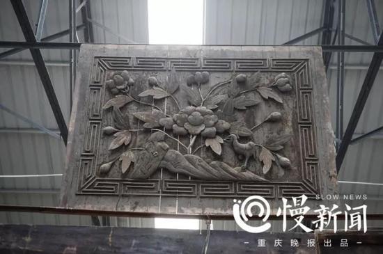 木板雕成花草图案,固定在大厅的墙顶中央。