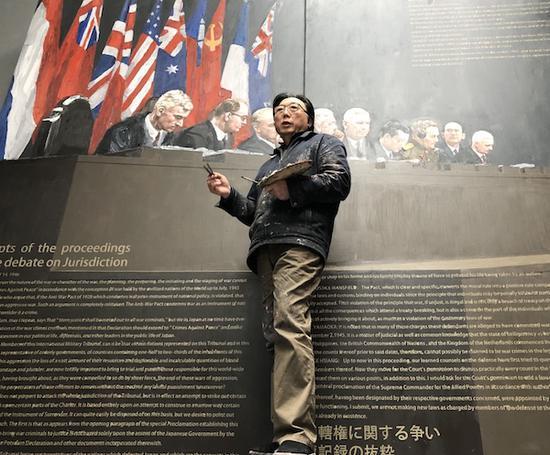 画家李斌和巨幅长篇油画《东京审判》局部