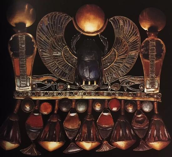 法老图坦卡蒙的胸饰   图案主题包括:展翅圣甲虫、上下埃及王之名、生命之符、荷鲁斯之眼以及莲花和纸莎草边饰   古埃及第十八王朝,约公元前1323年