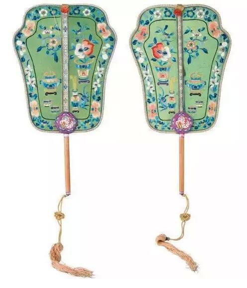 这把扇为清宫女性用品。纨扇的檀木柄上浅刻花纹,竹制的扇边有细致的软包,典雅精细,绿绸地上刺绣,博古瓶供花卉,寓意岁岁平安。