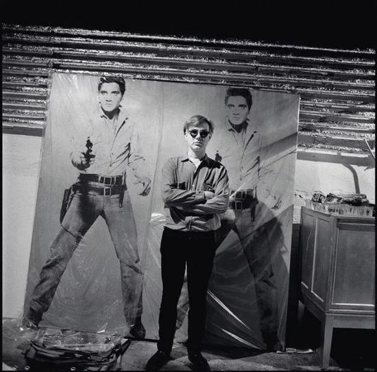 艺术品:? 2018The Andy Warhol Foundation for the Visual Arts, Inc。 / Licensed by Artists Rights Society (ARS),照片:? Bruce Davidson/Magnum Photos。安迪-沃霍尔与《双面猫王》 于工作室的合影,约1964年