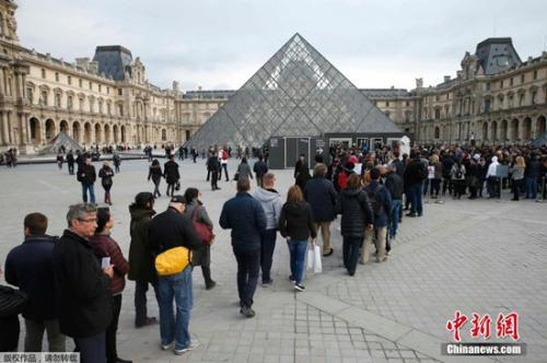 游客在法国巴黎的卢浮宫前排队等待参观。