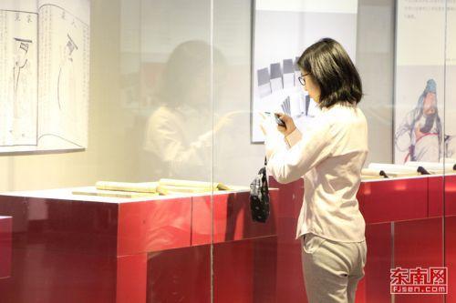 游客一遍观赏古籍一边拍照留念