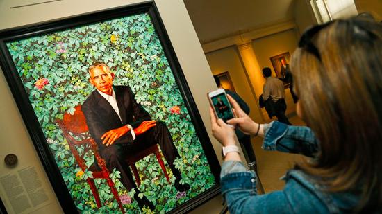 奥巴马肖像。作者Kehinde Wiley为黑人艺术家。背景的花枝象征着奥巴马的生平:芝加哥的菊花、夏威夷和印度尼西亚的茉莉花、肯尼亚的非洲百合,以及象征爱情的玫瑰花。华盛顿国家肖像美术馆(National Portrait Gallery)