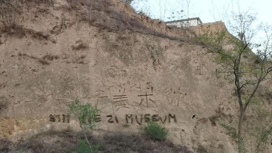 """写着""""石节子美术馆""""的黄土崖。新京报记者 王巍 摄"""