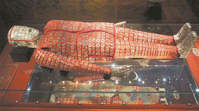 赵眜丝缕玉衣入殓复原全貌图,通过反光玻璃清晰可见丝缕玉衣下的垫玉璧。