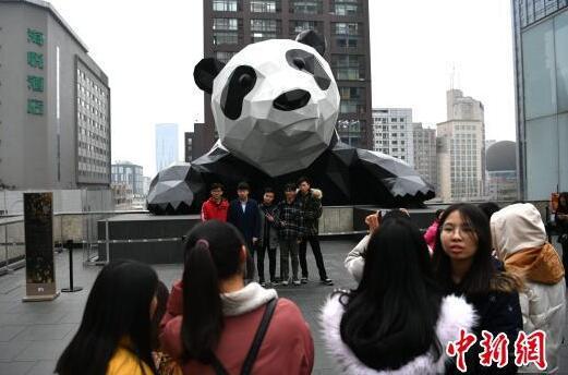 在大熊猫雕塑前合影的市民。 张浪 摄