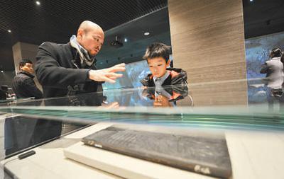 工作人员在向小朋友讲解木雕版孔子圣迹图 (人民视觉 杨国庆摄)