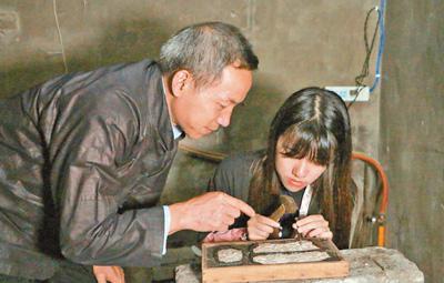 非遗传人吴水根(左)在指导徒弟制作银器。本报记者 史一棋摄
