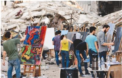 图为8月16日,在叙利亚首都大马士革,年轻画家们在耶尔穆克难民营废墟前作画。