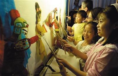 昨日,邯郸博物馆,小朋友们体验皮影戏表演。图/视觉中国