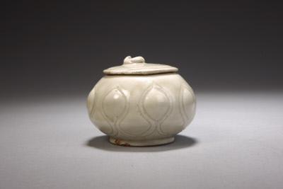 """定窑白釉刻划花莲瓣纹""""官""""字款盖罐,五代,高6.7cm,口径5cm,足径4.9cm。故宫博物院藏。"""
