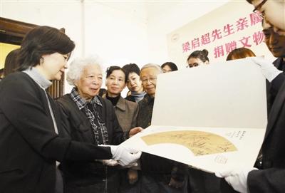 梁柏有女士(左二)向与会嘉宾介绍捐赠的藏品。王津摄