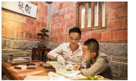 〈图一〉林志坚先生在给下一代讲解古钱知识,这就是一种传承