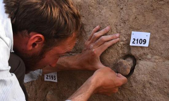 考古学家正在尝试从Eninnu神庙墙壁上取下一枚陶锥