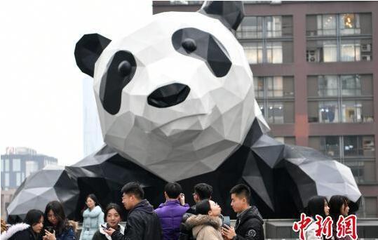 一些情侣来到大熊猫雕塑前合影。 张浪 摄