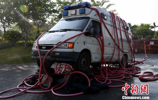 图为艺术家用报废的救护车、红色水管等创作雕塑作品《水满自溢》。 张斌 摄