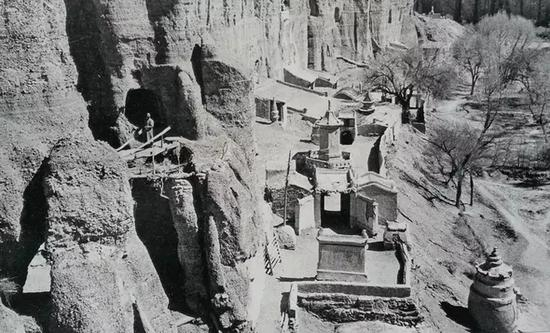 图14。肃榆林窟外景,1943年。罗寄梅摄。图中左侧桥上站立者为张大千