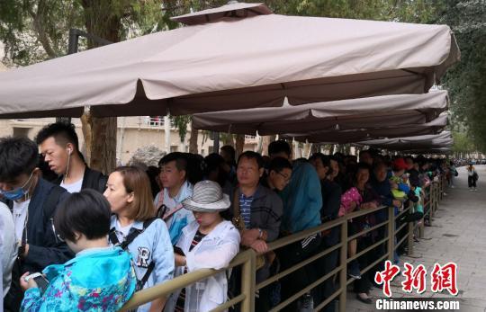 图为2018年8月中旬,莫高窟前等候参观的应急游客排成近1公里长队。(资料图) 冯志军 摄