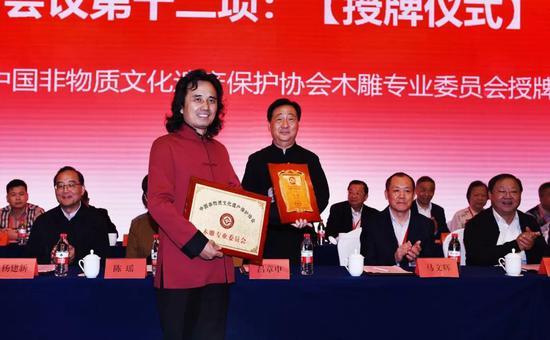 ▲吕章申先生为新当选的专委会主任黄小明授牌