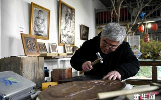 12月4日,在位于石家庄市德明古镇的工作室,郭海龙制作铁板浮雕作品。