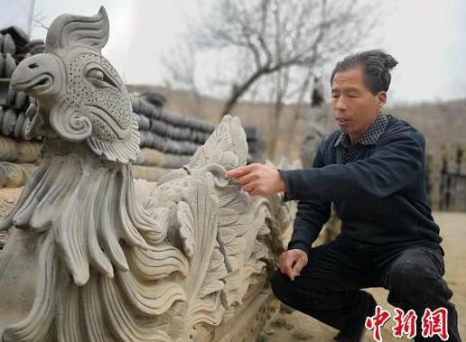 """图为刘泉泥塑的作品""""凤戏牡丹""""。 魏建军 摄"""