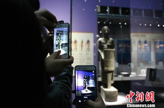 展览分为四大板块,图为展览中展出的赫纳特神像,吸引观众围观。 赵晓 摄