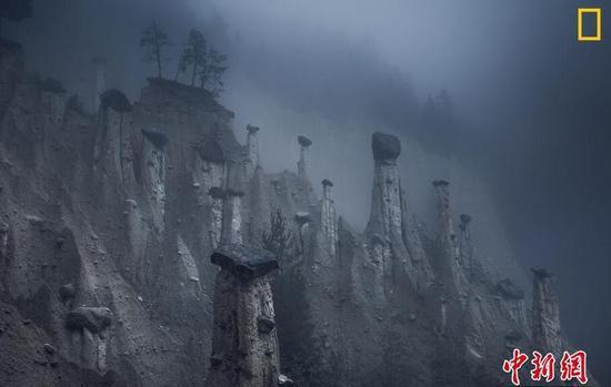 自然组第三名 摄影师:Marco Grassi 图片说明:意大利波尔扎诺自治省,这些天然砂塔顶上放着大石块。这奇怪的地形由多次的暴风雨和滑坡形成。