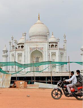 图为 2018 年 1 月 3 日拍摄的资料图片,显示了两名男子骑车经过位于印度班加罗尔 (Bangalore) 的泰姬陵模型。图片来源:法新社/曼珠纳特基兰。