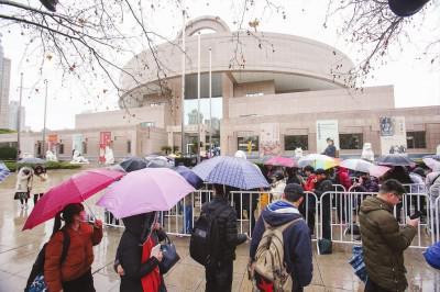 淅淅沥沥的小雨中,市民游客排队进馆参观。