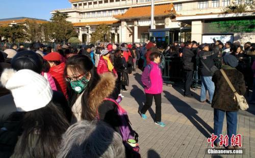 """资料图:11月下旬,主题为""""美在新时代""""的中国美术馆典藏精品特展正在举行。图为准备参观中国美术馆典藏精品特展的民众在美术馆外排起长队。中新社记者 满会乔 摄"""