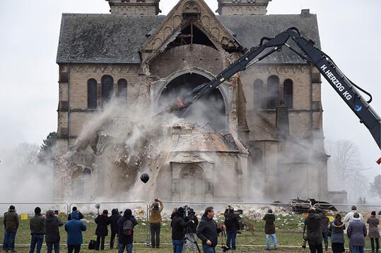 图为 2018 年 1 月 8 日拍摄的资料图片,显示了市民和新闻工作者目睹昔日神圣的圣兰伯特斯教堂被毁。图片来源:法新社/德意志新闻社/汉宁-凯泽。