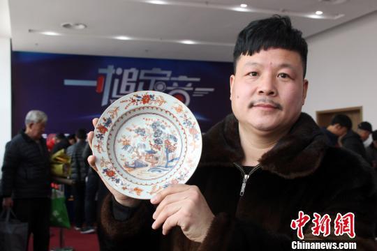 """藏友刘景民在展示""""晚清青花矾红描金花卉山水人物盘""""真品。 于俊亮 摄"""