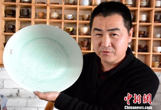 黄涛展示他自己工厂加工的克拉克瓷。 张金川 摄