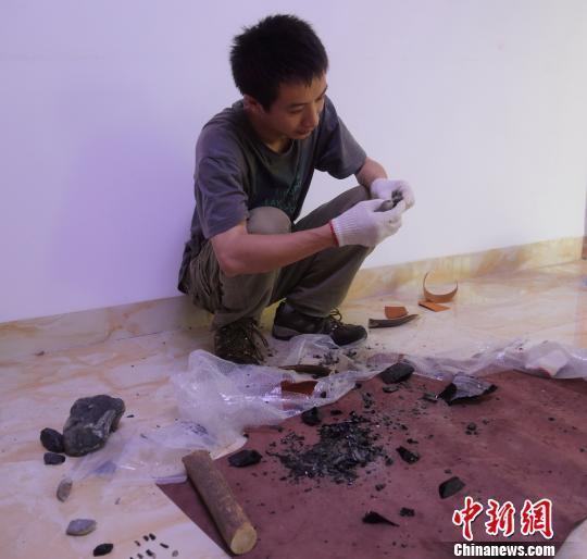 专家进行石器打制模拟实验。 钟欣 摄