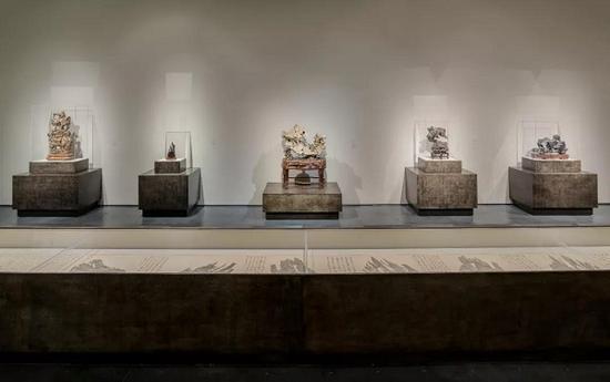 展览现场,从左到右:木雕太湖石,紫檀木雕刻石,太湖石,清代奇石,墨石