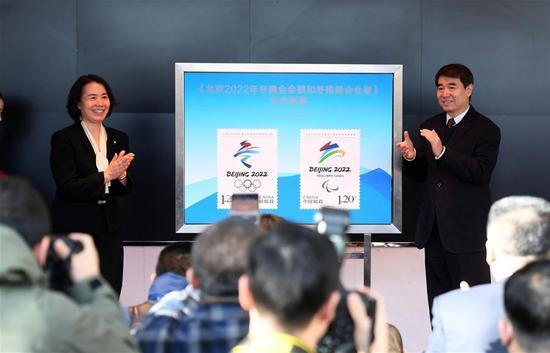 12月31日,北京冬奥组委秘书长韩子荣(左)与中国邮政集团副总经理李丕征共同揭晓《北京2022年冬奥会会徽和冬残奥会会徽》纪念邮票。新华社记者李俊东摄