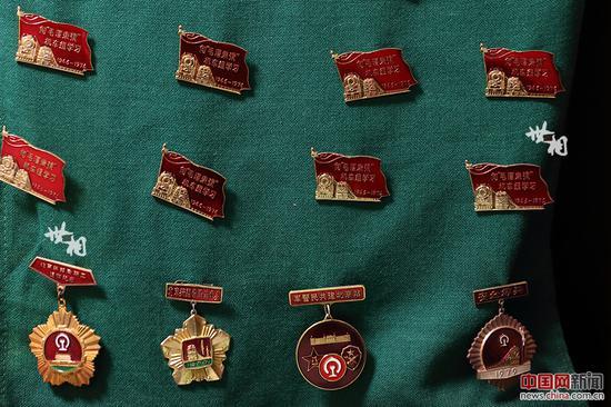 """在李志强收藏的各类胸章中,最多的是向""""毛泽东号""""机车组学习的胸章。"""