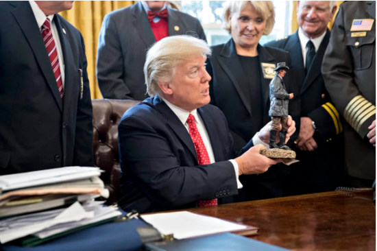 2017年2月7日,华盛顿特区白宫的椭圆形办公室内,特朗普手持与郡县警长会面时获得的一尊雕像礼物。图片:by AndrewHarrer – Pool/Getty Images