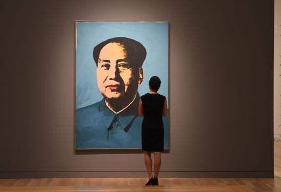 一位女士注视着安迪·沃霍尔的《毛泽东》。图片:TIMOTHY A。 CLARY/AFP/Getty Images