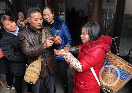 杨治明(左二)为当地村民鉴别刚刚捡到的硒玉。