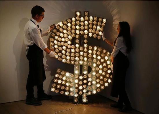苏富比员工为一幅由Tim Noble和Sue Webster创作的《$》调整位置。图片:Adrian Dennis/AFP/Getty Images