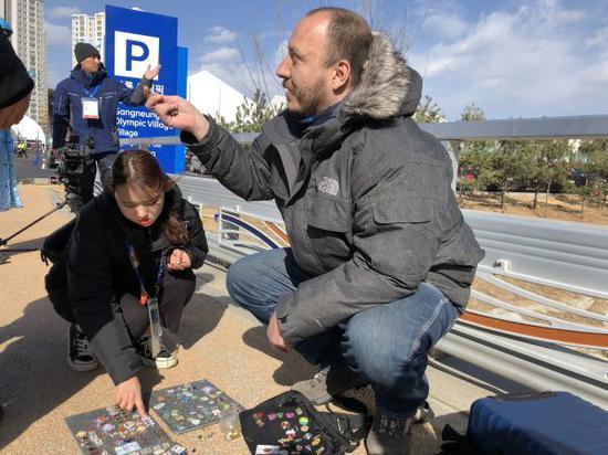 图为2018年2月11日路过的志愿者及工作人员在塞尔西奥-洛佩斯身旁挑选徽章。(参考消息网记者 任韬衡摄)