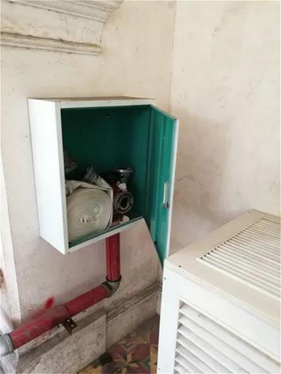 消火栓箱被空调室外机罩遮挡,且栓口安装在消火栓箱轴侧,无法正常使用