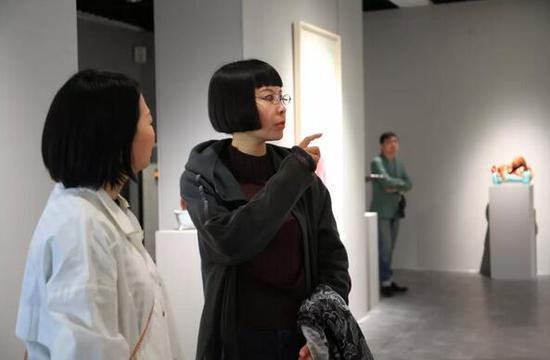 展览艺术家丁荭(右一)与艺术家米玉明交流