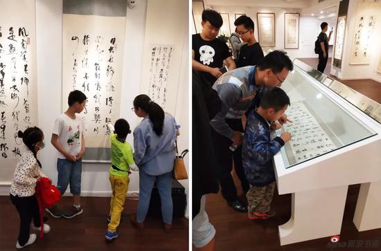 家长带着小朋友也来观展啦。小朋友在很认真的认识草书。