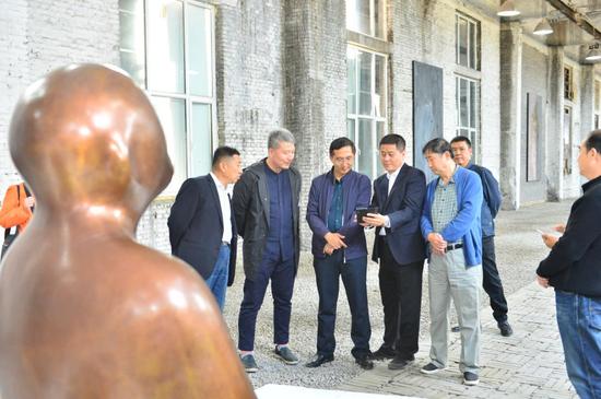 来宾们在王振林的雕塑作品《悟空》前进行交流