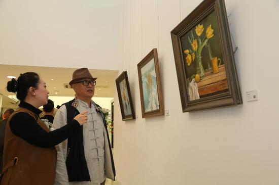 张岩向杨先介绍自己的油画作品